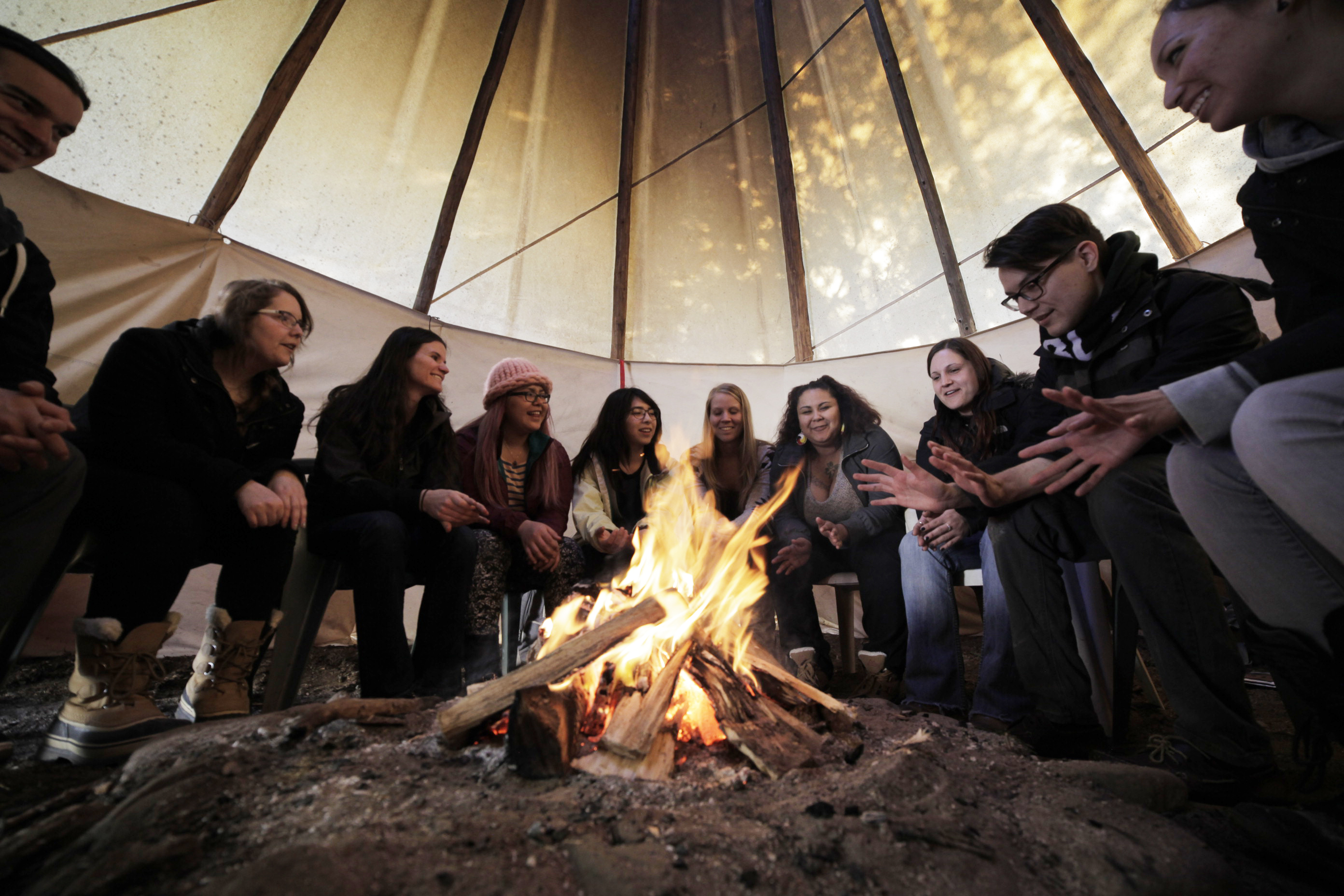 A group of individuals sitting around a fire