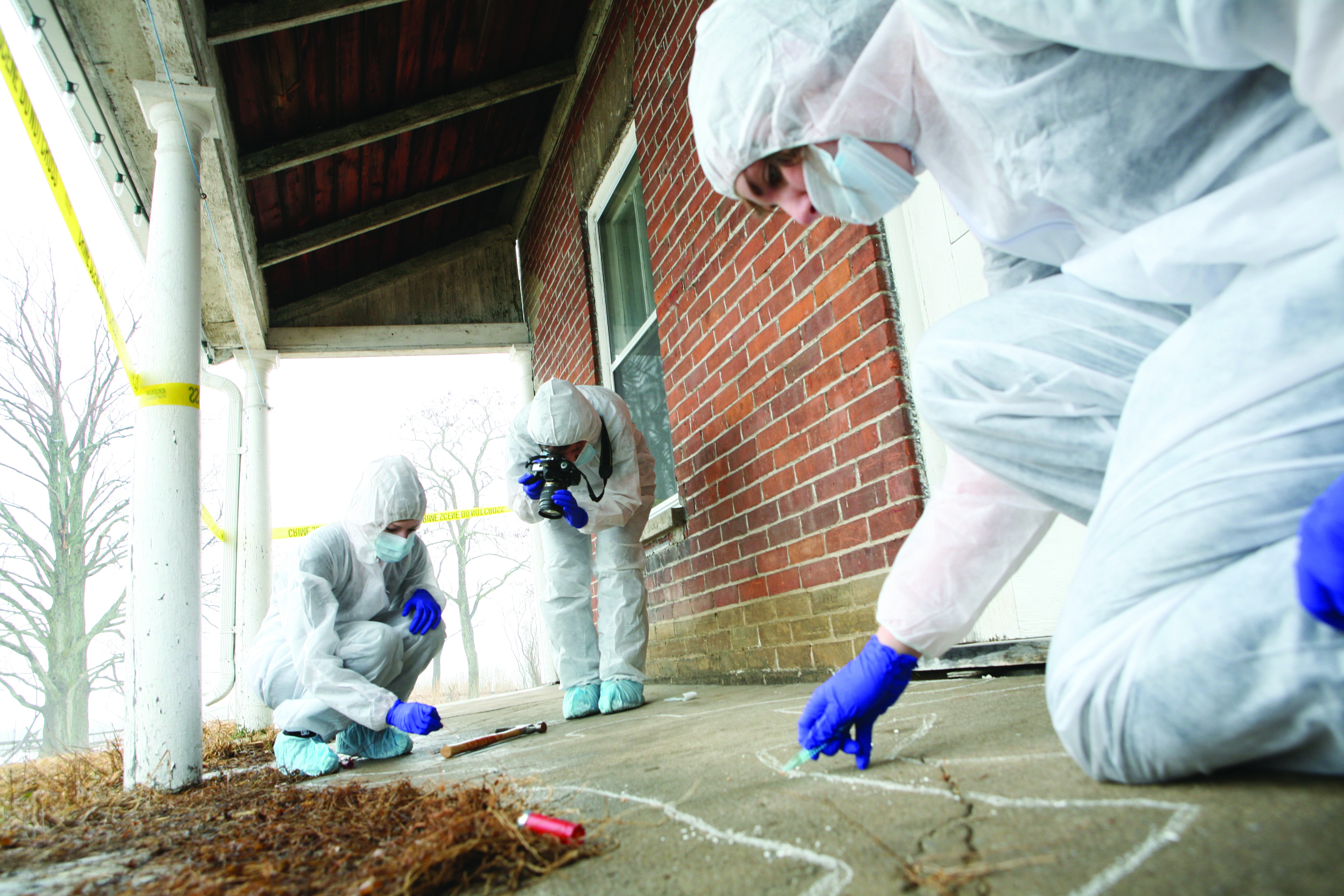 Four Individuals in white lab coats inspecting a crime scene