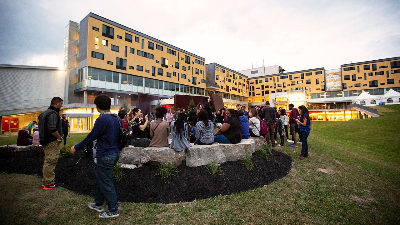Gzowski College with several students by the Gzowski firepit