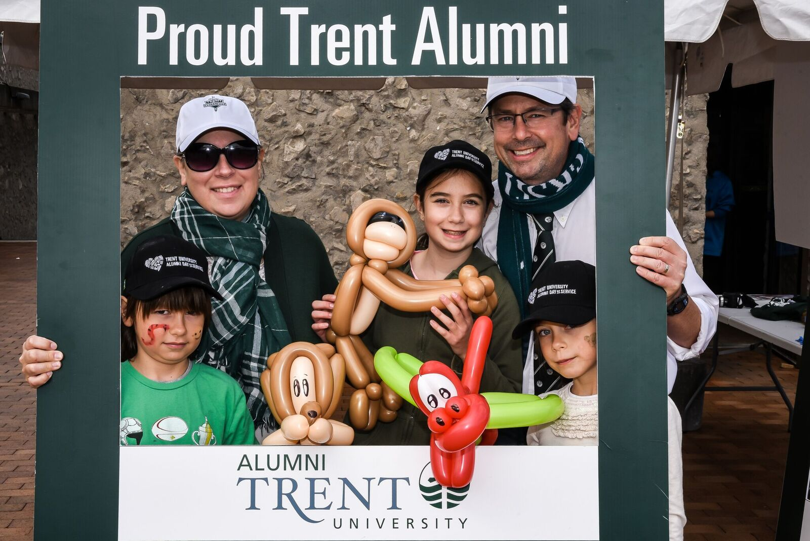 a proud Trent family gathering under the alumni photo frame