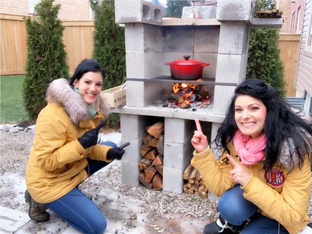 Maddie and Kiki standing infront of an outdoor wood stove
