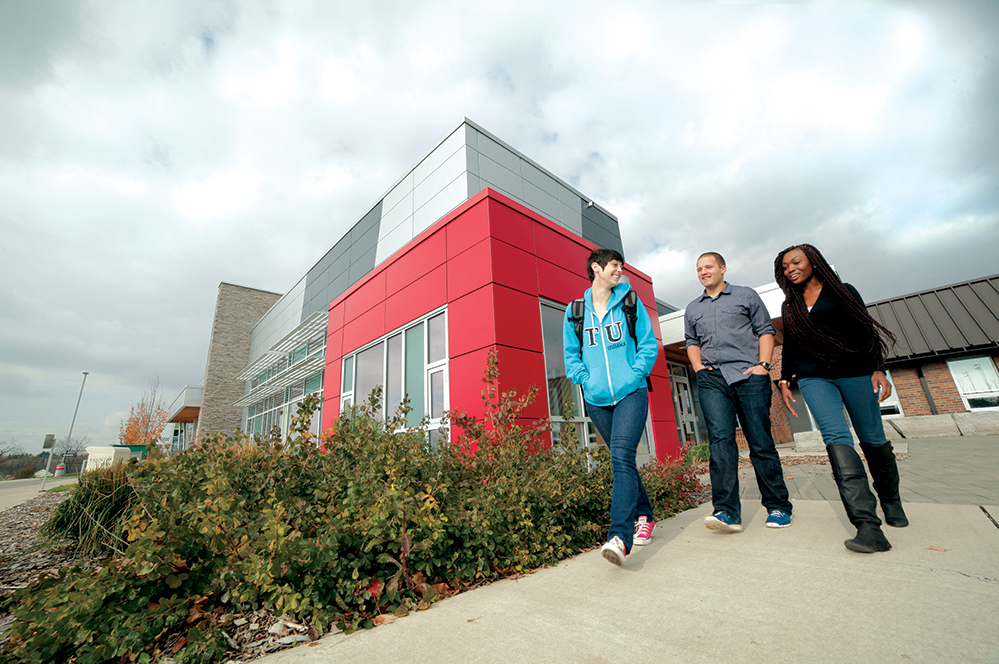Three students walking in front of a red building on the Durham Campus