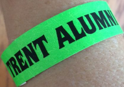 "green wristband with ""Trent Alumni"" on an arm"