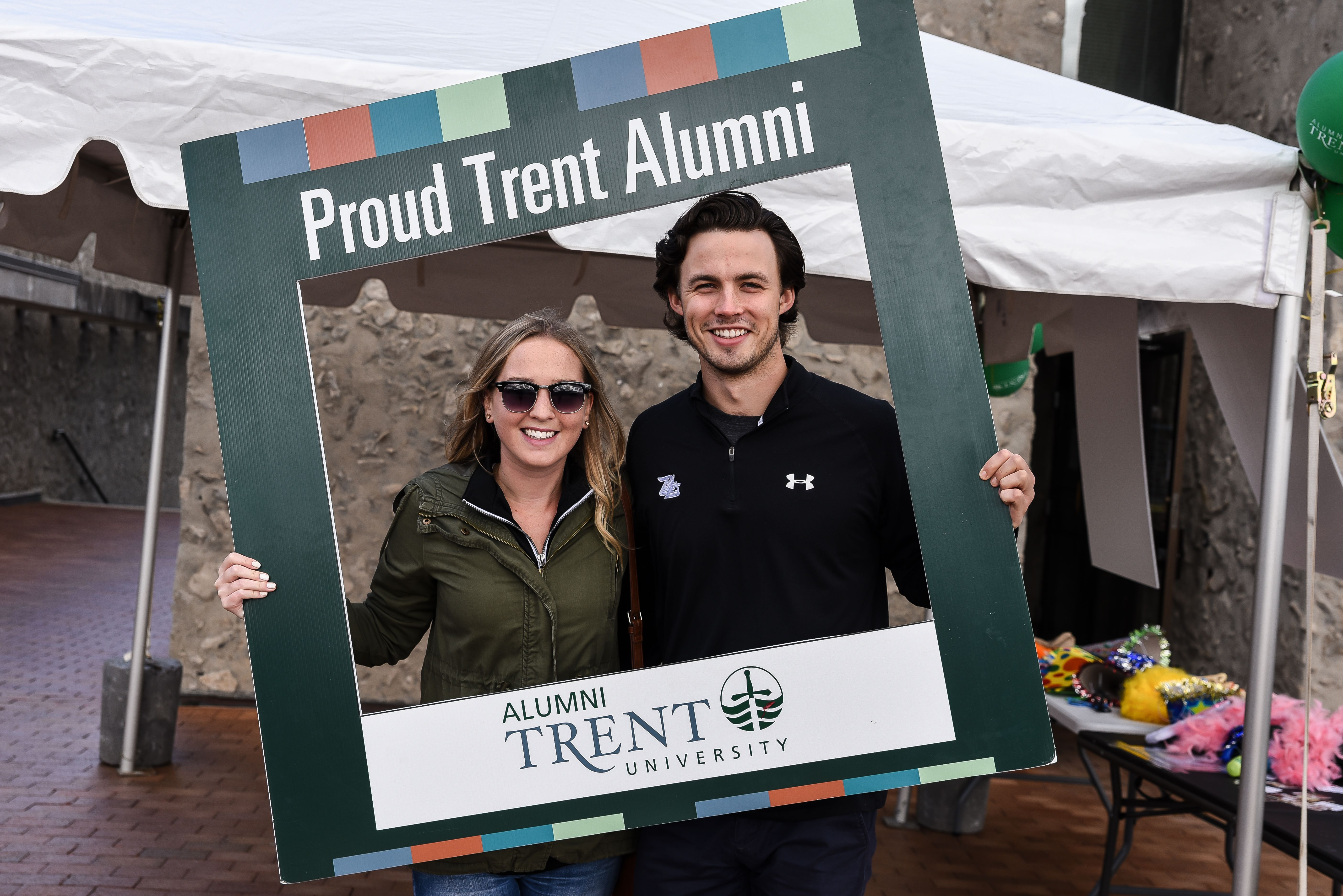 a couple holding the Proud Trent Alumni sign