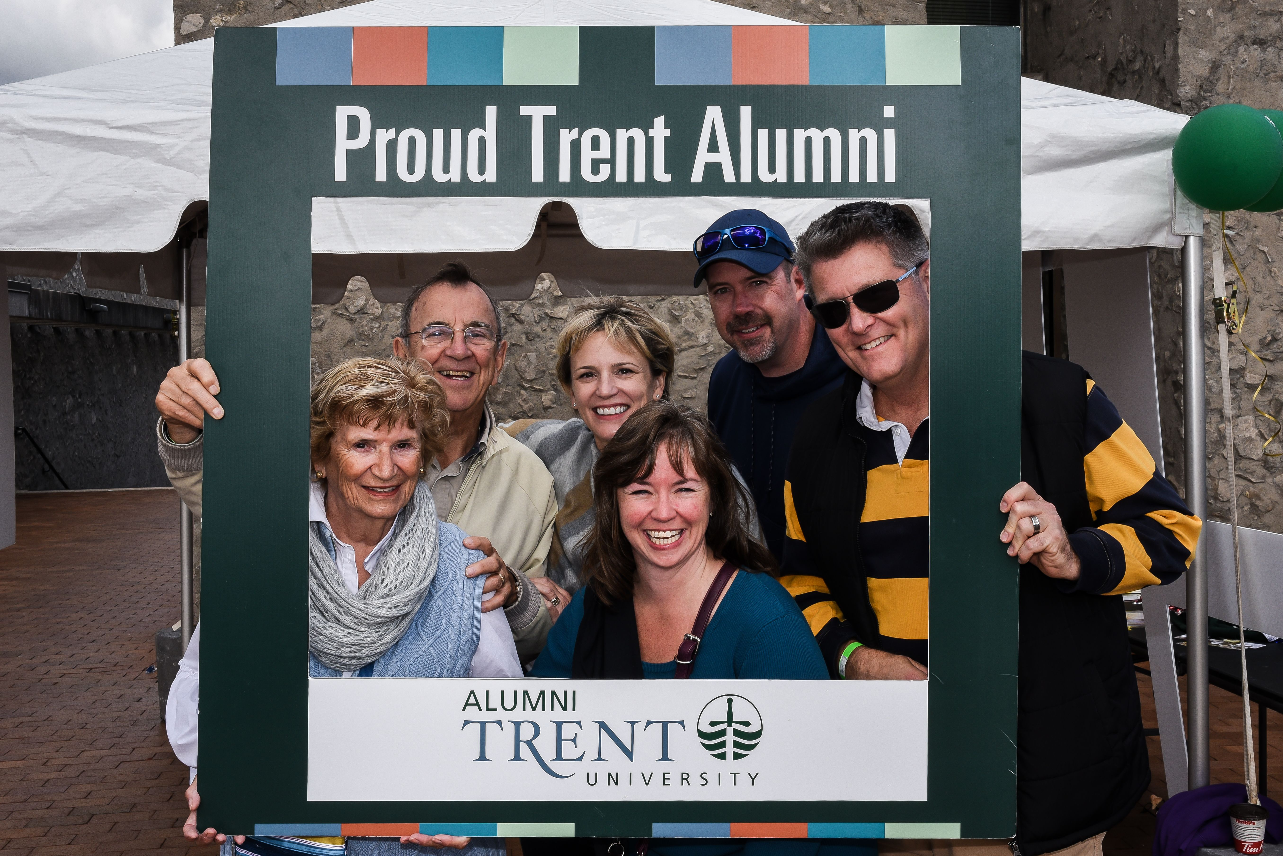a group of individuals holding the proud Trent Alumni sign
